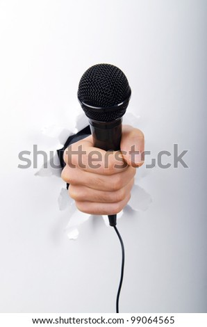 Hand holding microphone through hole in paper - stock photo