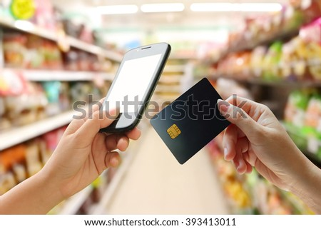 hand holding mobile and credit card with blur shop background - stock photo