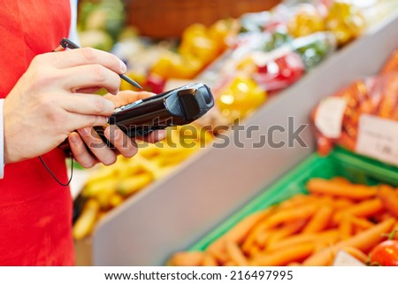 Hand holding mobile data registration terminal in a supermarket - stock photo