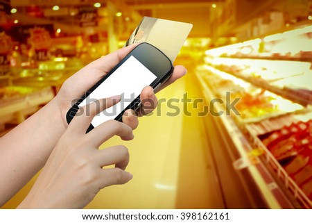 hand holding mobile phone and credit card with blur store background - stock photo