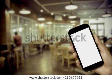 Hand holding mobile phone on blurred coffee shop made vintage style - stock photo