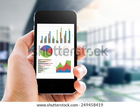 hand holding mobile phone with analyzing graph - stock photo