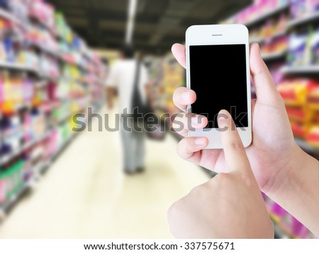 Hand holding mobile phone with blank screen with blur supermarket background, Online delivery concept. - stock photo