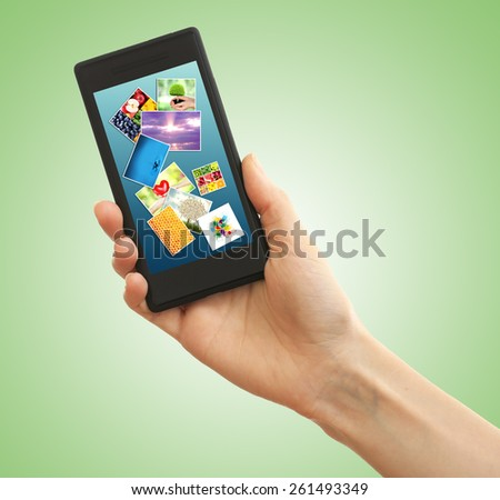 Hand holding mobile phone with different pictures on screen, green background - stock photo
