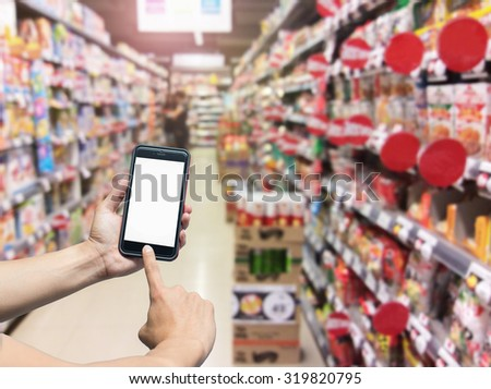 hand holding mobile smart phone on Supermarket blur background,business lifestyle concept - stock photo