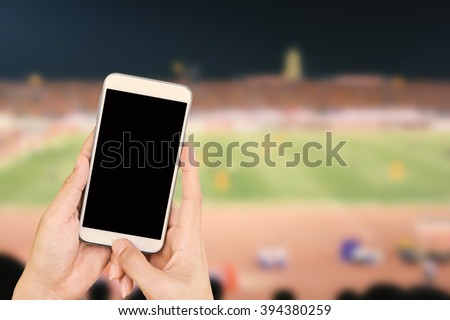 Hand holding mobile smart phone with black screen, blur image of a football field as background. - stock photo