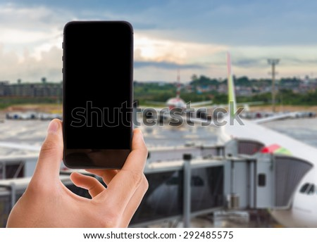 Hand holding mobile smart phone with black screen on airport background - stock photo