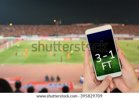 Hand holding mobile smart phone with score on black screen, blur image of a football field as background. - stock photo