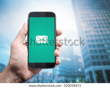 Hand holding mobile smartphone with message on a screen. E mail icon, Office buildings background - stock photo