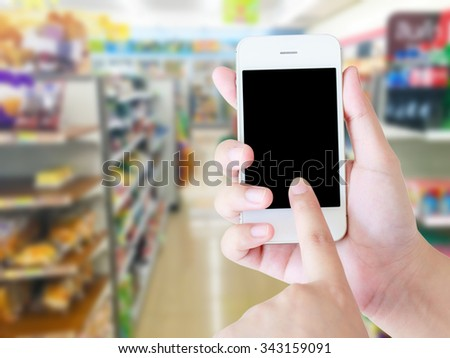 Hand holding mobile with blur supermarket shelves background, Online shopping concept. - stock photo