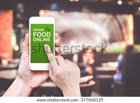 Hand holding mobile with Order food online with blur restaurant background, food online business concept.Leave space for adding your text. - stock photo