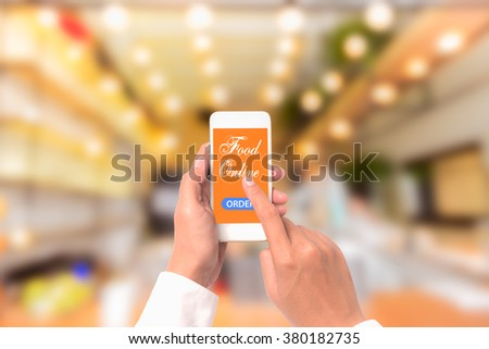 Hand holding mobile with Order food online with blur restaurant background, food online business concept.Leave space for adding your text - stock photo