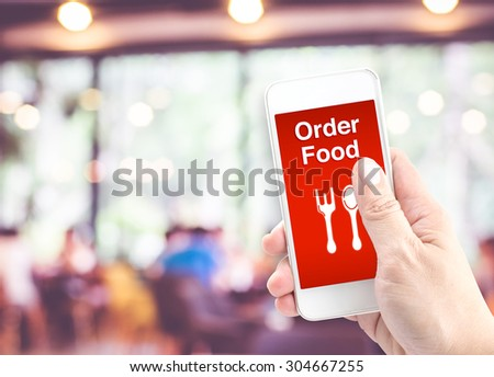 Hand holding mobile with Order food with blur restaurant background, Order food online business concept. - stock photo