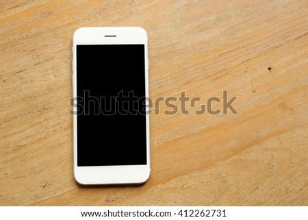 Hand holding mockup smartphone on desk wooden - stock photo