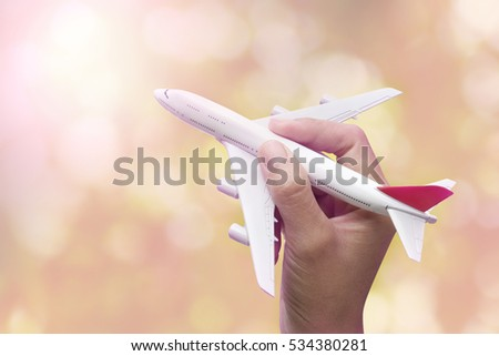 hand holding model of airplane on bokeh background.