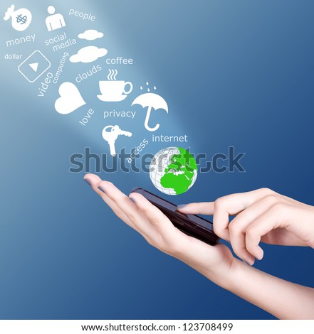 Hand holding modern mobile phone and social media symbols flying away - stock photo