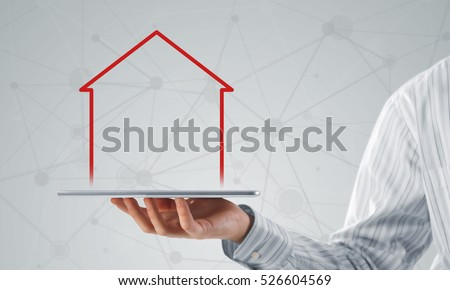 Hand holding modern tablet and house sign on screen
