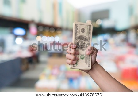Hand holding money american dollars on shopping mall background - stock photo