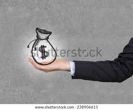 hand holding money drawing bag on gray background - stock photo