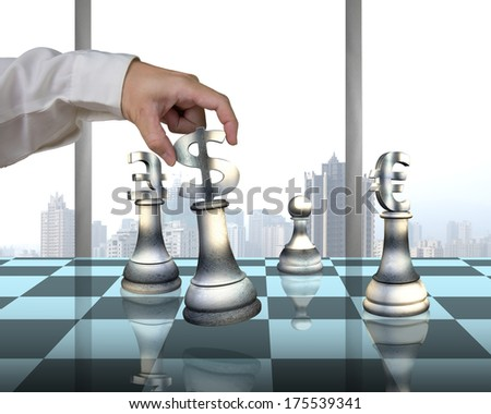 Hand holding money symbol others on table playing chess with city view - stock photo
