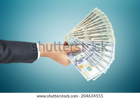 Hand holding money - United states dollar (USD) banknotes - stock photo