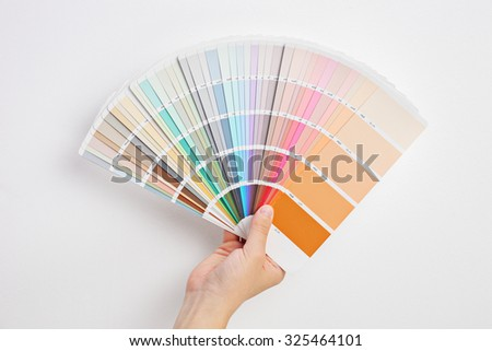 Hand holding multicolored cardboards spread against a gray wall