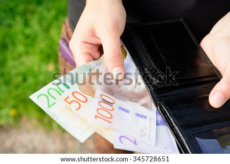 Hand holding new swedish bank notes and wallet. NOTE: the new 2015 model.