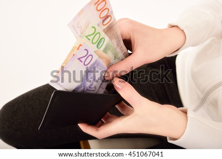 Hand holding new swedish bank notes and wallet. NOTE: the new model.