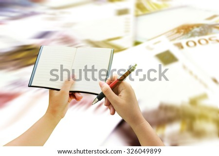 hand holding notebook and pen with blur euro banknote background - stock photo
