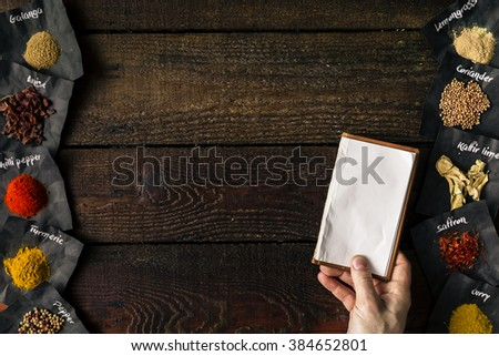 Hand holding notebook on old wooden table with spices. - stock photo