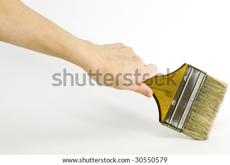 Hand holding old paintbrush on white - stock photo