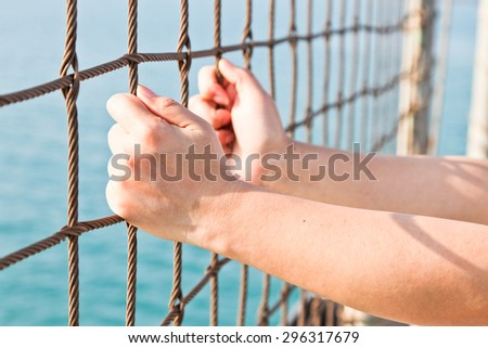 Hand Holding On Chain Link Fence soft focus - stock photo
