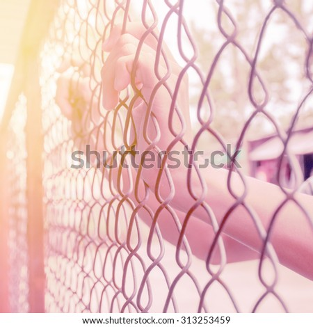 Hand holding on chain link fence, Vintage filter effect - stock photo