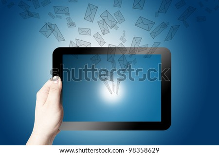 Hand holding on digital tablet with 3D mail icon coming from the screen on blue background - stock photo