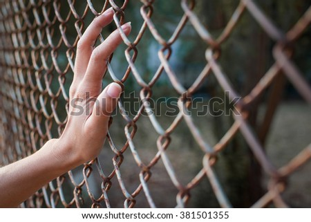 Hand holding on fence