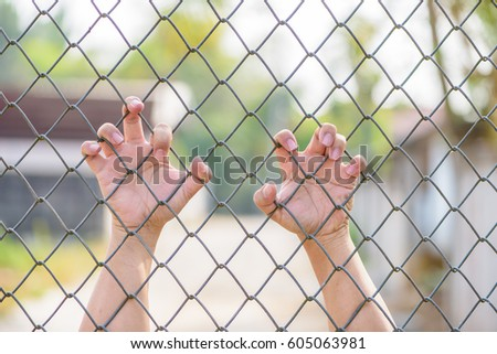 Hand holding on Metal Grille