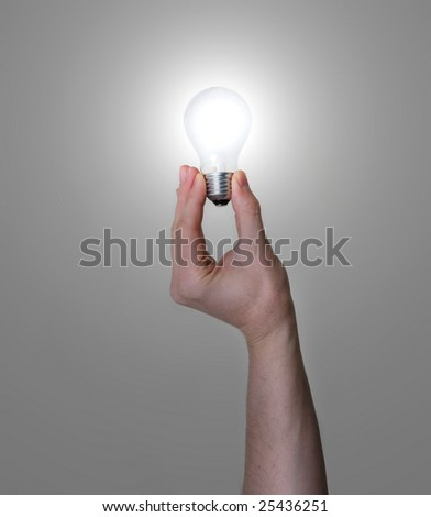 hand holding one glowing light bulb between fingers