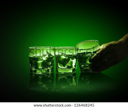 Hand holding one of three glasses of green absinth with fume going out - stock photo