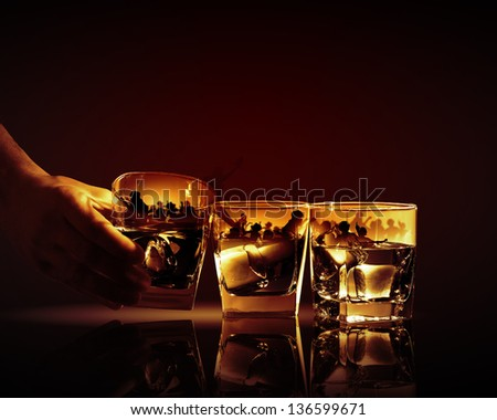 Hand holding one of three glasses of whiskey with ice and party illustration in - stock photo