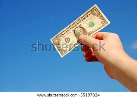hand holding one US dollar against blue sky - stock photo