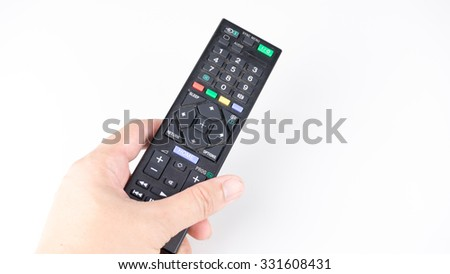 Hand holding or pressing button on remote controller for TV or media device. Isolated on white background. Slightly de-focused and close-up shot. Copy space.