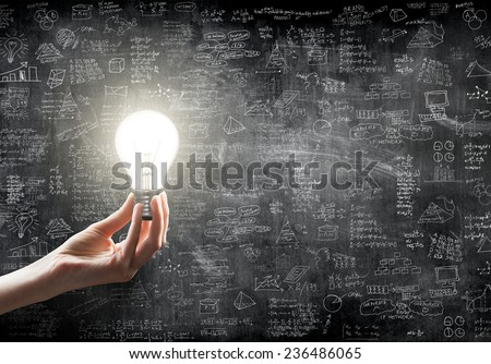 hand holding or showing a light bulb in front of  business idea concept on wall backboard blackground - stock photo