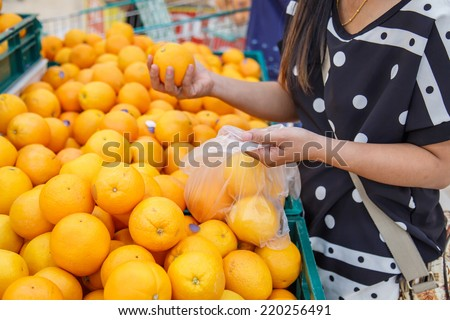 Hand holding orange in department store