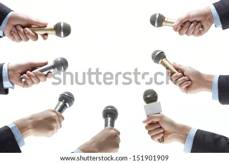 hand holding out a microphone isolated on white background - stock photo