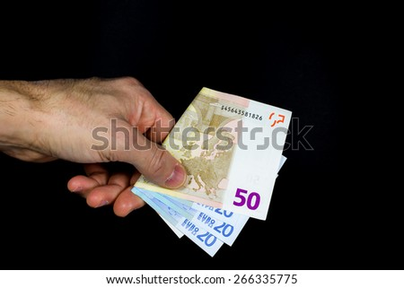 hand holding out some banknotes, on a dark background - stock photo