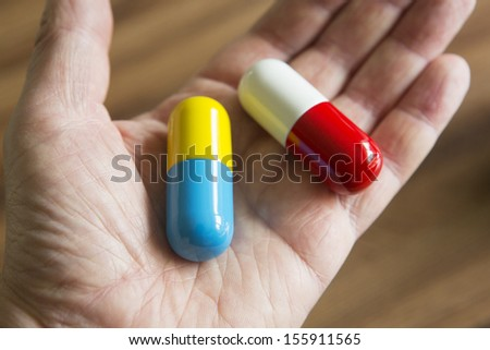 Hand Holding Over-sized Medication Capsules - stock photo