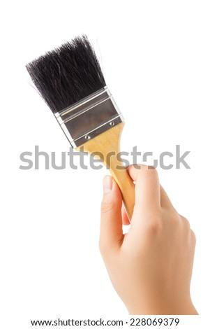 Hand holding paint brush isolated on white background. - stock photo