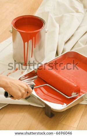 Hand holding paint roller in tray with painting supplies on drop cloth.