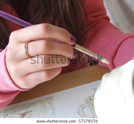 Hand holding paintbrush - stock photo
