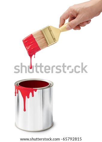 hand holding paintbrush after dipping into its bucket - stock photo